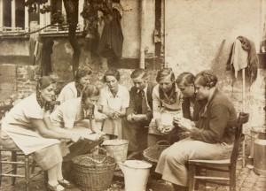 """Sechs Kirmesmädchen, unterstütz von einem Kirmesburschen, beim Kartoffelschälen für den """"3. Kirmestag"""" (Dienstag) 1935."""