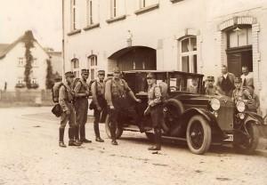 """Auch das gehörte zum """"Moos"""". Die Gastwirtschaft war wahrscheinlich schon vor der """"Machtergreifung"""" der NSDAP 1933 Treffpunkt Krofdorfer Anhänger dieser Partei. Hier rückt - wahrscheinlich bereits 1932 - ein Gruppe SA-Männer zu einer auswärtigen Veranstaltung aus. Nähere Umstände zur Entstehung des Bildes sind allerdings unbekannt."""
