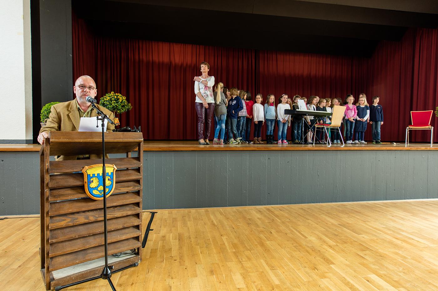 Moderator der Veranstaltung Rüdiger Soßdorf im Hintergrund der Schulchor der Krofdorfer Grundschule